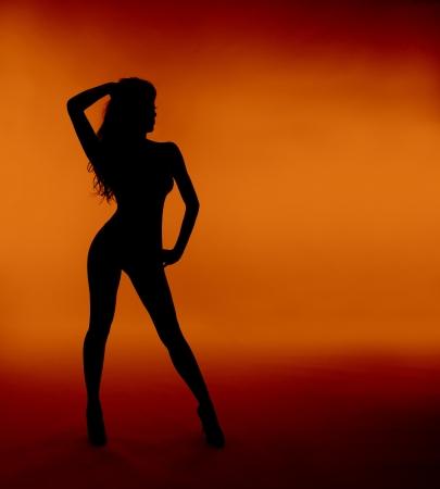 erotico: silhouette donna sexy piedi sfondo arancione