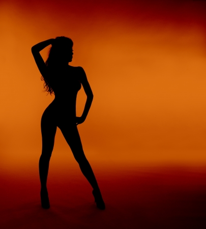 nude body: woman sexy silhouette standing  orange background Stock Photo