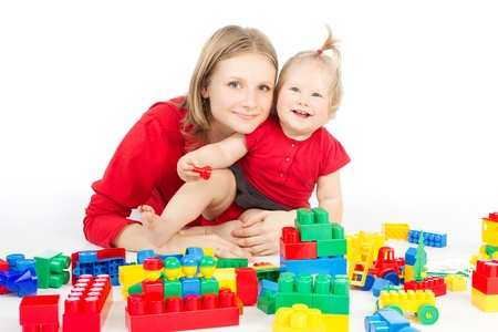 baby sit: Mother and daughter playing together building blocks over white Stock Photo