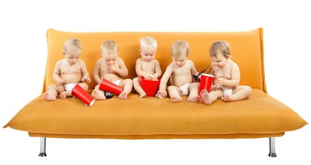Group of children sitting on sofa and eating popcorn. Isolated white photo