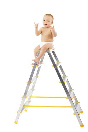 escaleras: Adorable niño sentado en la cima de la escalera de mano, levante las manos. Fondo blanco Foto de archivo