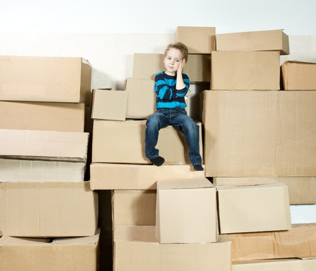 reflective child sitting on the top of stack packed boxes photo