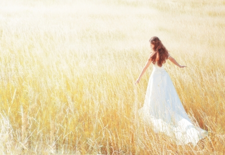 wind dress: woman walking in the sunny meadow on summer day touching grass