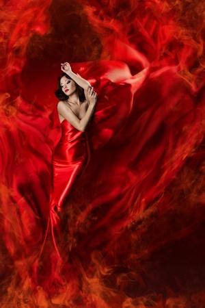 Hermosa mujer en vestido rojo de seda ondeando como una llama de fuego. Mirando hacia abajo. Foto de archivo