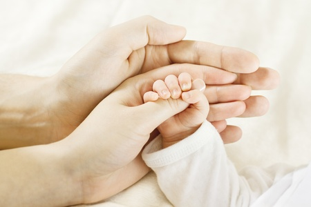 Closeup of baby  hand into parents hands. Family concept