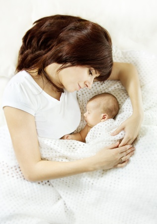 baby mother: Mother lying down and embracing sleeping newborn baby. Protection and mothers love concept.
