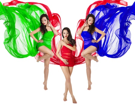 Three woman dance in red, green, blue flying dress. Over white background. RGB color concept. photo