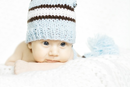 indigo: Newborn baby closeup portrait in blue woolen hat over white soft background. Indigo eyes