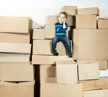 over packed: Riflettente bambino seduto sulla cima del mucchio di scatole di cartone imballati. Archivio Fotografico