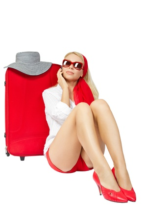 Beautiful woman sitting next to red suitcase and talking on phone vacation suitcase talking on phone. Isolated over white background
