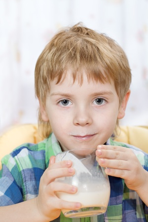 boy with milk mustache after drinking from glass photo