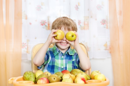 Happy boy playing with apples in front of the table with fruits. Indoors portrait photo