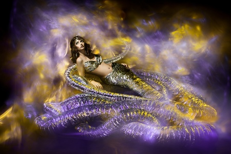 Beautiful woman in fantasy dress. Snake fashion dress stylish. Abstract background. Artwork photo