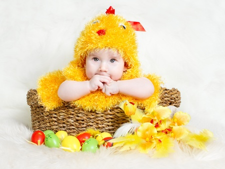 Baby in Easter basket with eggs in chicken costume. Easter holiday concept: nest with baby chick photo