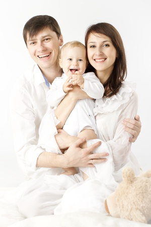 Happy family holding smiling baby over white background Stock Photo - 13841649