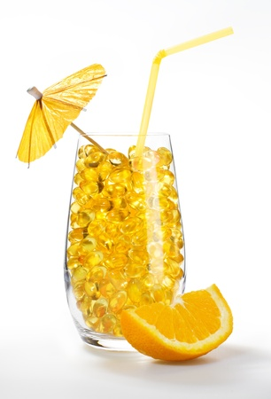 Healthy vitamin cocktail: yellow oil pills in translucent glass with slice of orange, straw and umbrella photo