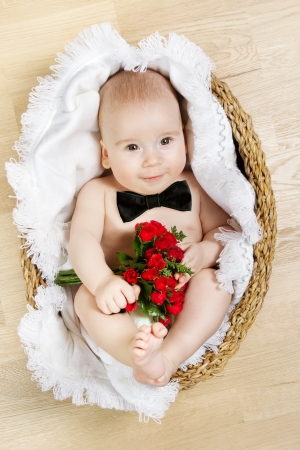 adorable baby holding flowers and wearing butterfly tie, lying in basket. Young gentleman concept. photo