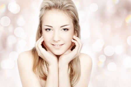 Beautiful smiling young woman. Closeup portrait over abstract shiny background Stock Photo - 13841651