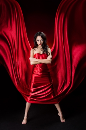 Mysterious  woman in red waving silk dress over black background. photo
