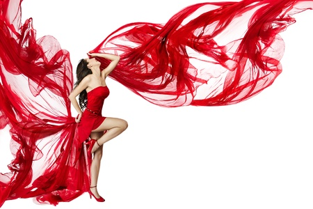 Beautiful woman dancing in red dress flying on a wind flow over white background photo