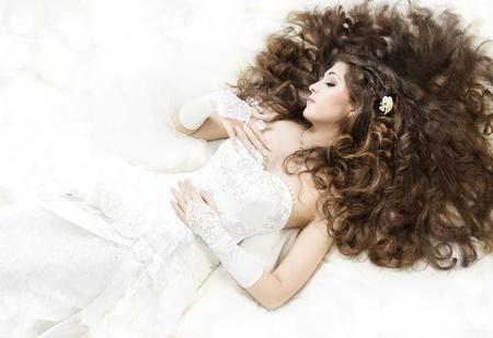 Dreaming bride with long curly hair lying down over white. Sleeping beauty. High angle view. photo