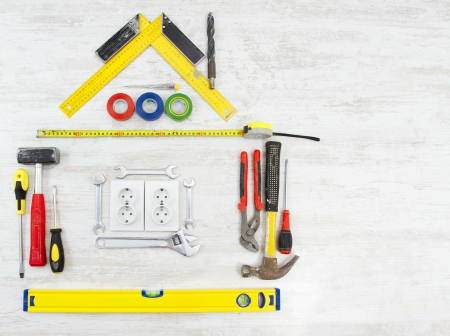 home improvements: Tools in the shape of house over wooden background. Home improvement concept. Stock Photo