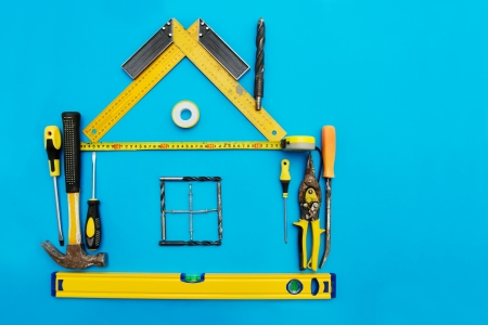Tools in the shape of house over blue background. Home improvement concept. photo