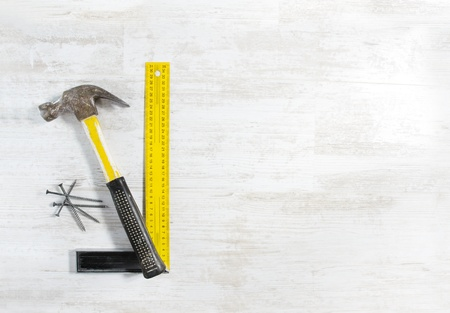 Hammer with nails and ruler. Tools set for construction work over wooden background. photo