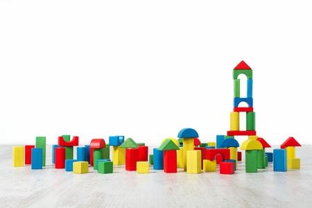 juguetes de madera: Bloques de construcci�n de juguete sobre el piso en el interior vac�o blanco. Childrenroom dise�o.