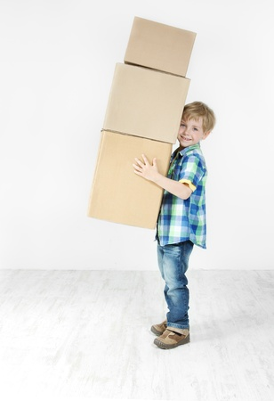 on the move: Boy holding pyramid of carton boxes. Packing up to move. Growth concept.