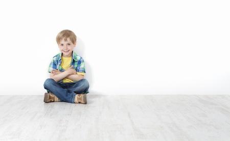 mani incrociate: Handsome bambino seduto sul pavimento appoggiato muro bianco. Gambe e le mani incrociate.