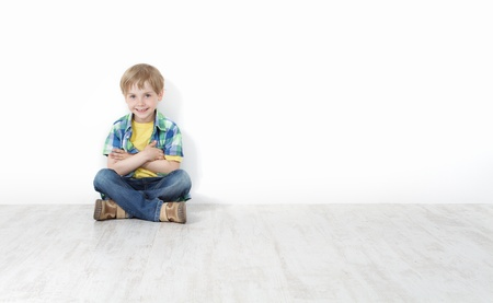 Handsome little boy sitting on floor leaning against white wall. Legs and hands crossed. Stock Photo - 14117034