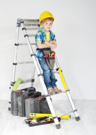 Little boy handyman with helmet and tool belt on stepladder. Equipment for construction works photo