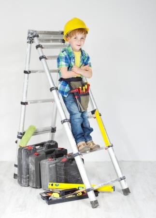 stepladder: Little boy handyman with helmet and tool belt on stepladder. Equipment for construction works Stock Photo