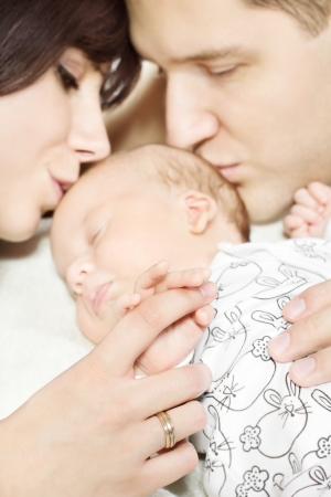 newborn baby: Parents with newborn baby lying down and kissing child  Family and parenting concept