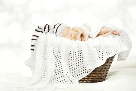 Sleeping newborn baby in woolen hat lying in basket with blanket over white soft background  photo