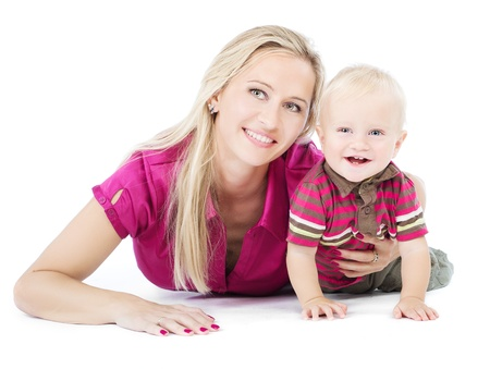 Happy mother playing with one year child lying on the floor over white Imagens