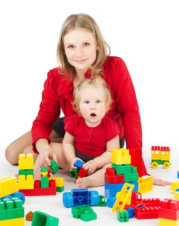 Mother and daughter playing together  blocks over white photo