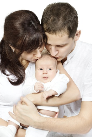 Parents kissing newborn baby over white background. Family love concept. Stock Photo