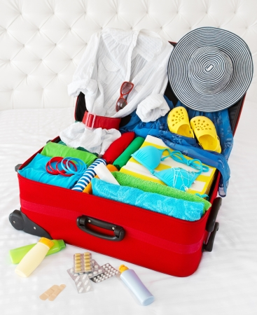 belongings: Travel suitcase packed for vacation with personal belongings. Concept. Preparation for holidays in sea resort: what to pack to the luggage. Isolated on white