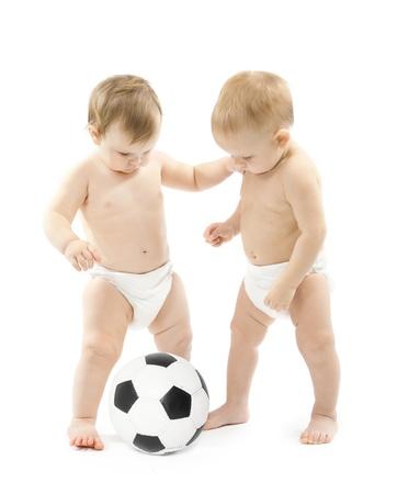 Dos bebés jugando a la pelota de fútbol sobre fondo blanco los niños el desarrollo físico Foto de archivo - 14207507