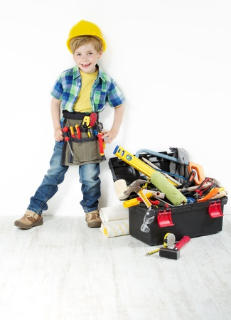 laborers: Little boy handyman in hard hat and tool belt next to construction toolbox full of tools