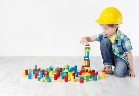 Boy in hard hat playing with blocks  building city  Development and construction concept photo