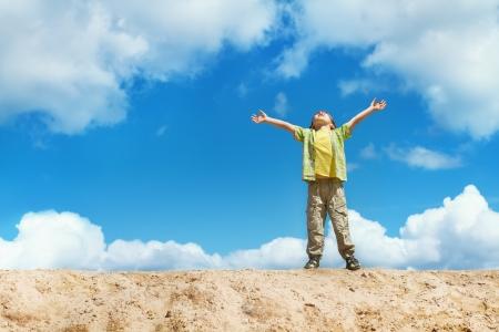 manos levantadas al cielo: Ni�o feliz de pie en la parte superior con las manos levantadas a la felicidad y el concepto de la libertad