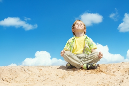 meditating: Happy child sitting in lotus position over bllue sky on the top  Happiness and freedom concept