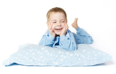 Smiling child lying down with pillow over white background Stock Photo - 14312471