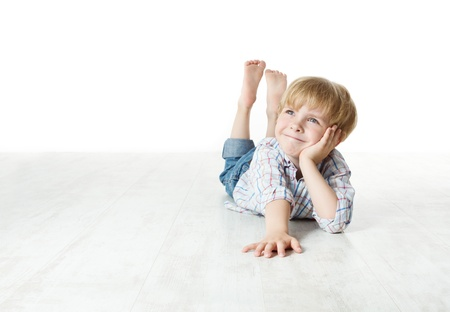 dream planning: Thinking smiling little boy lying down on floor and looking up to the side