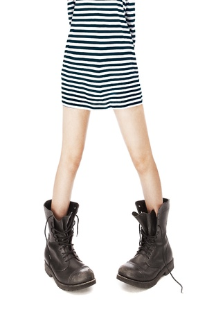 informal clothes: old leather military boots, striped singlet on woman feet Stock Photo