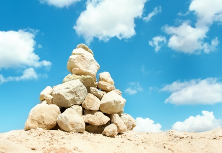 Pyramid of stones stacked outdoors over blue sky background photo