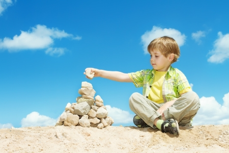 Child putting last stone part to complete pyramid sitting outdoors over blue sky. Solution concept.